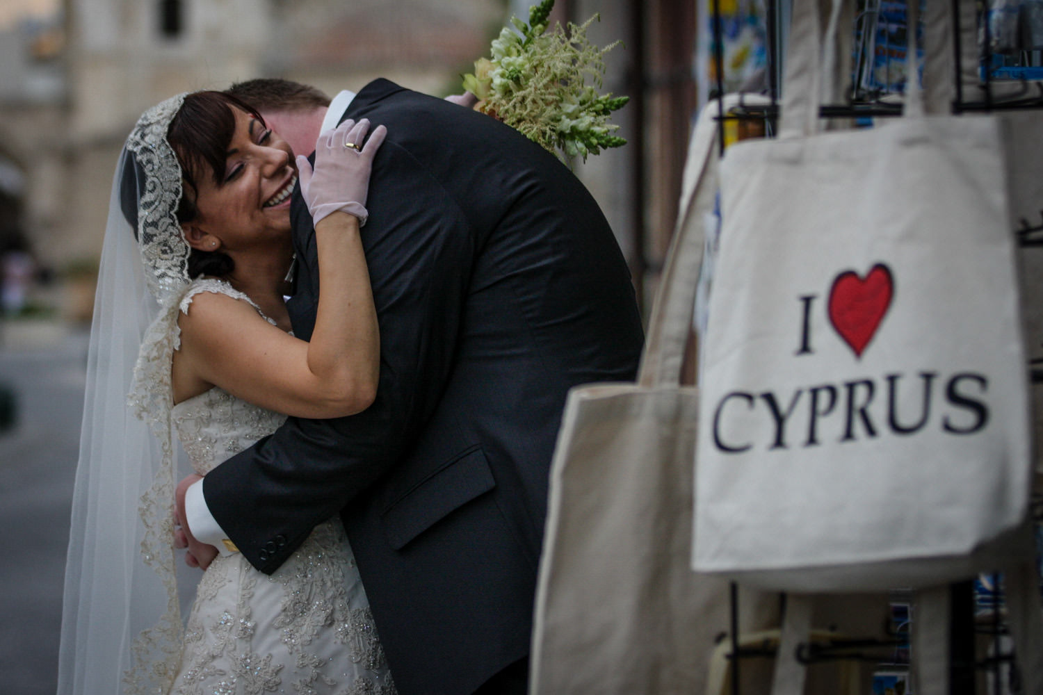 Bride and groom laughing in street in Larnaca Cyprus with bag saying I love Cyprus