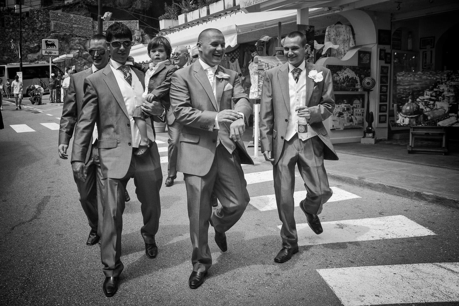 Groom and ushers walking through the streets of Positano