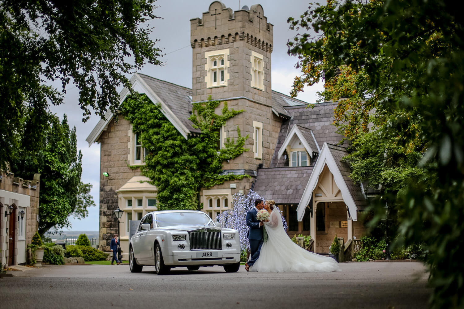Bride and groom with white Rolls Royce in front of West Tower