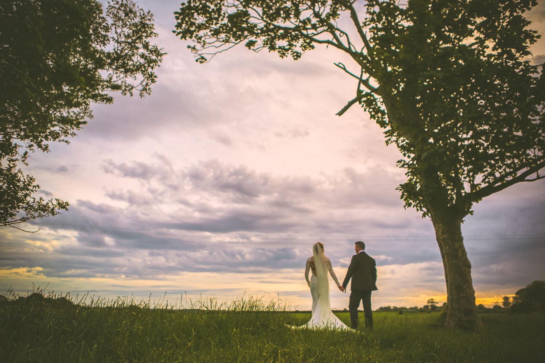 Bride in Berta wedding dress looking at sunset with groom Lancashire wedding