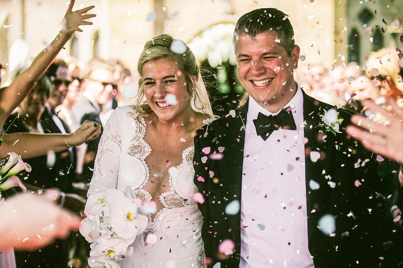 Bride and groom leaving church under confetti at Lancashire wedding St Nicolas church Wrea green
