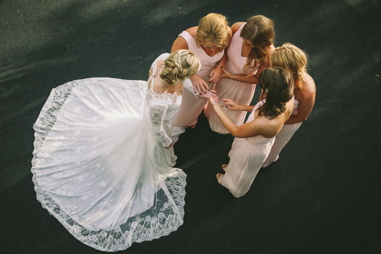 Bride in Berta dress showing off wedding ring to bridesmaids at lLancashire wedding in Wrea Green