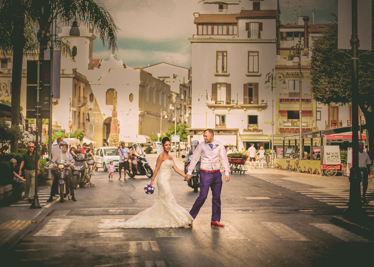 Bride and groom crossing busy road in Sorrento wearing wedding dress from wedding