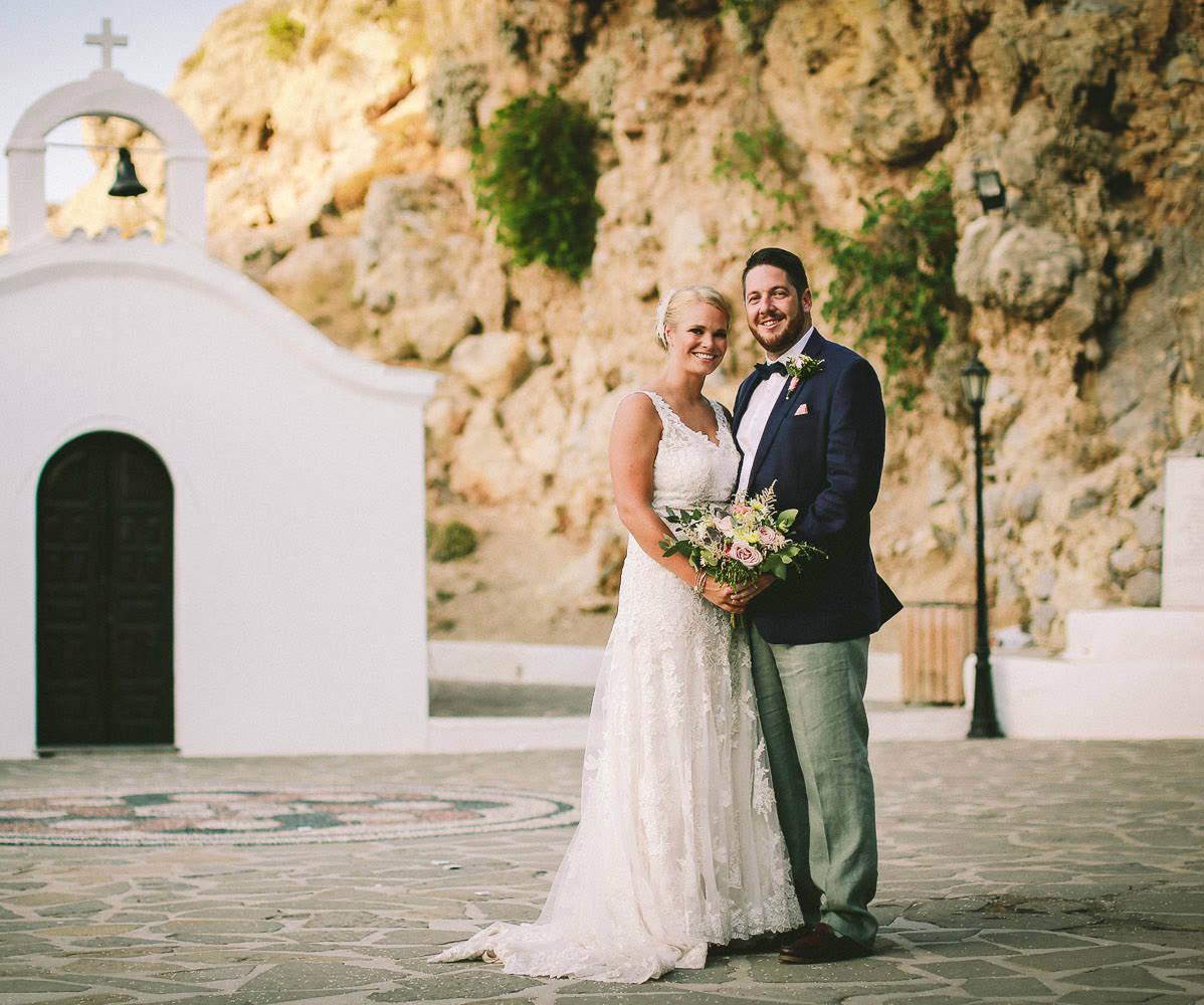 St Pauls bay, lindos wedding. Bride and groom at chapel on beach