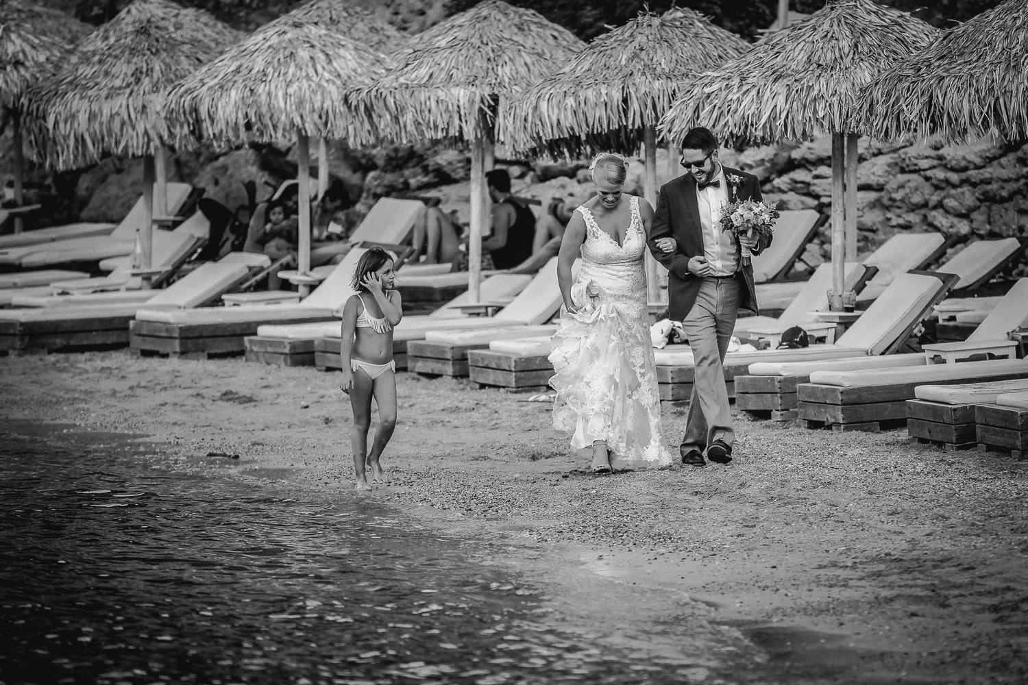 Lindos wedding photography, black and white photo of bride and groom walking on St Pauls Bay beach