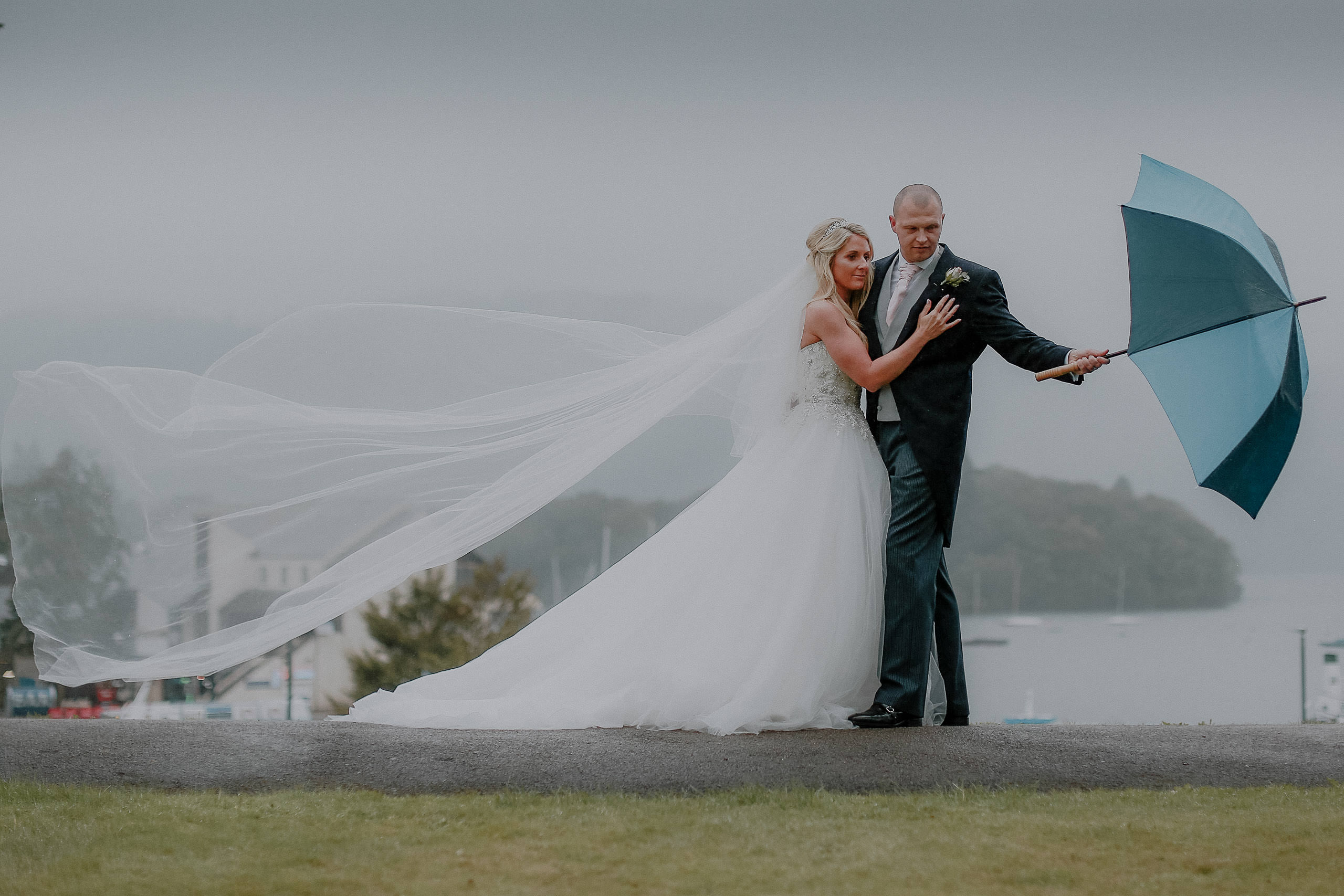Bride and groom in rain with umbrella at Lake Windermere from Laura Ashley hotel wedding