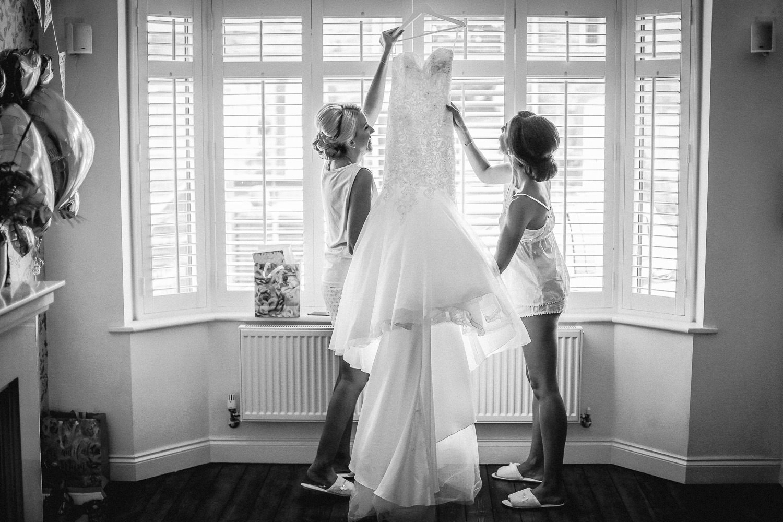 two girls hanging up Mori Lee fishtail wedding dress down