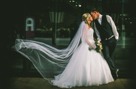 Liverpool Hilton wedding Bride and Groom kissing with vail blowing
