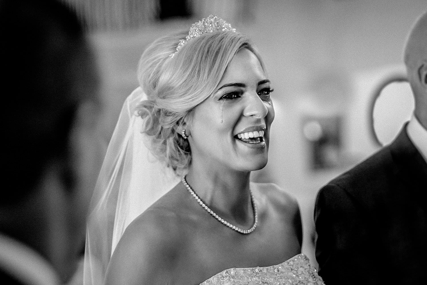 Photo of bride smiling as tear rolls down face
