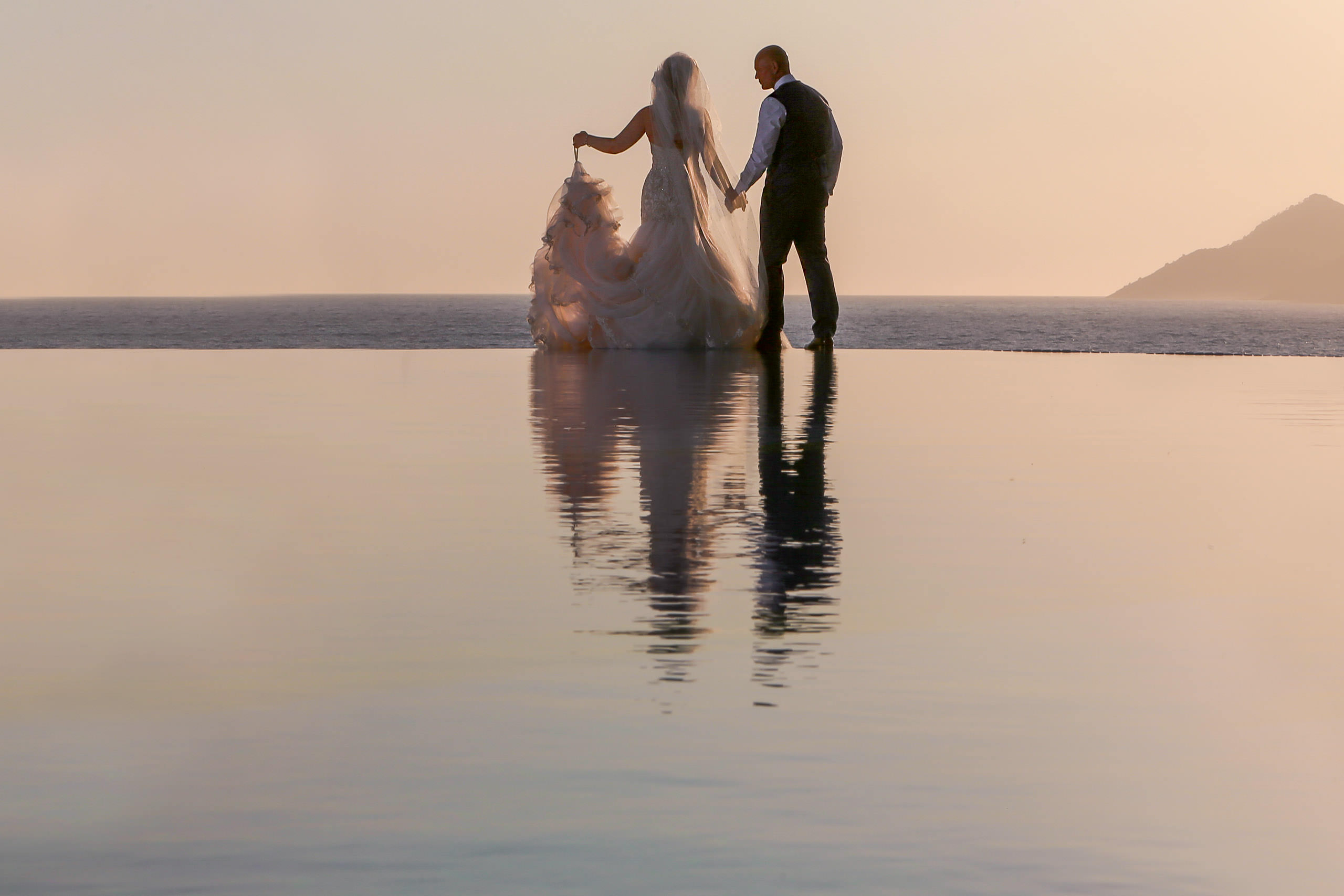Destination wedding photography. Bride and Groom silhouette at sunset with swimming pool reflection