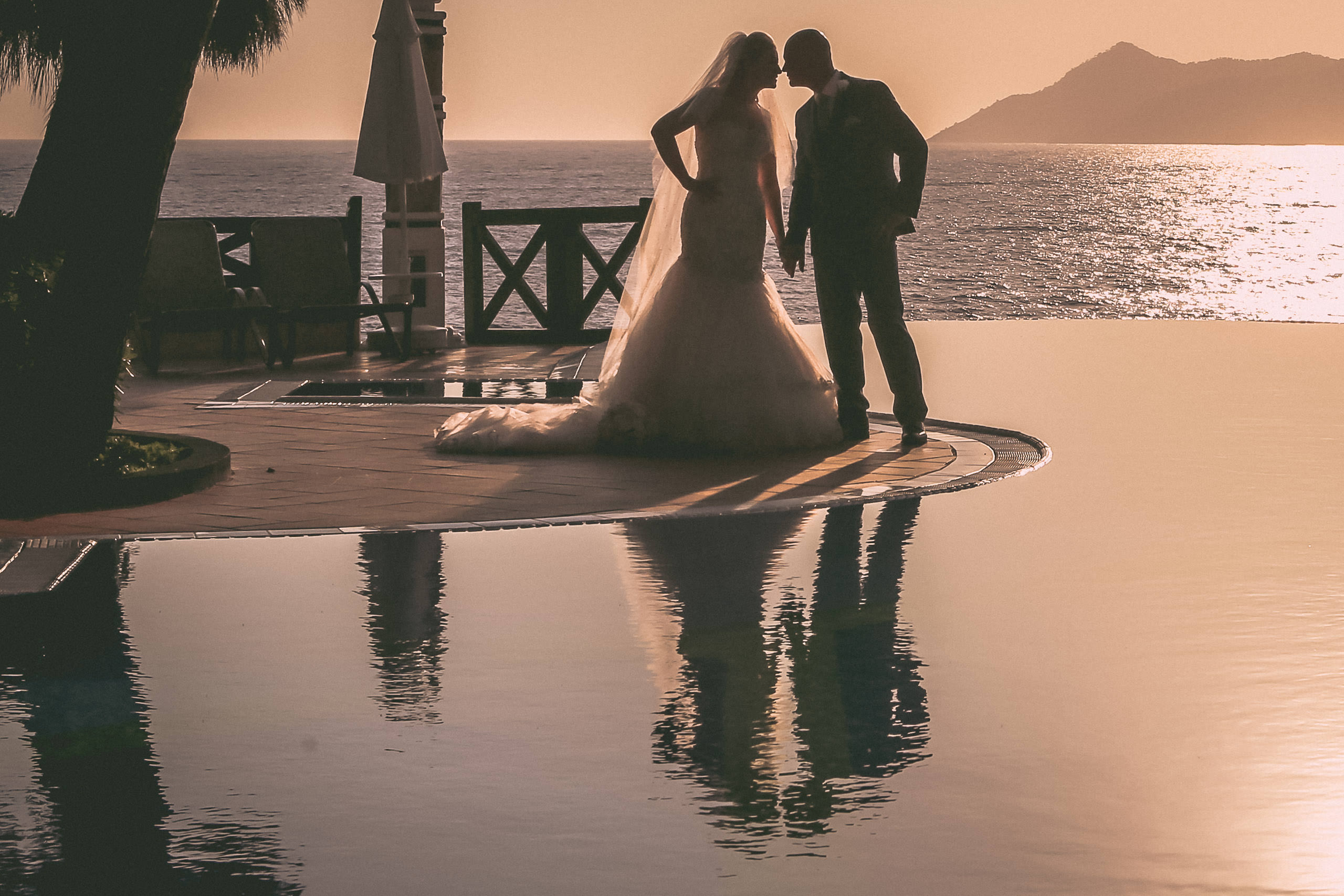 Sunset wedding with bride and groom at infinity pool Liberty Lykia world Turkey