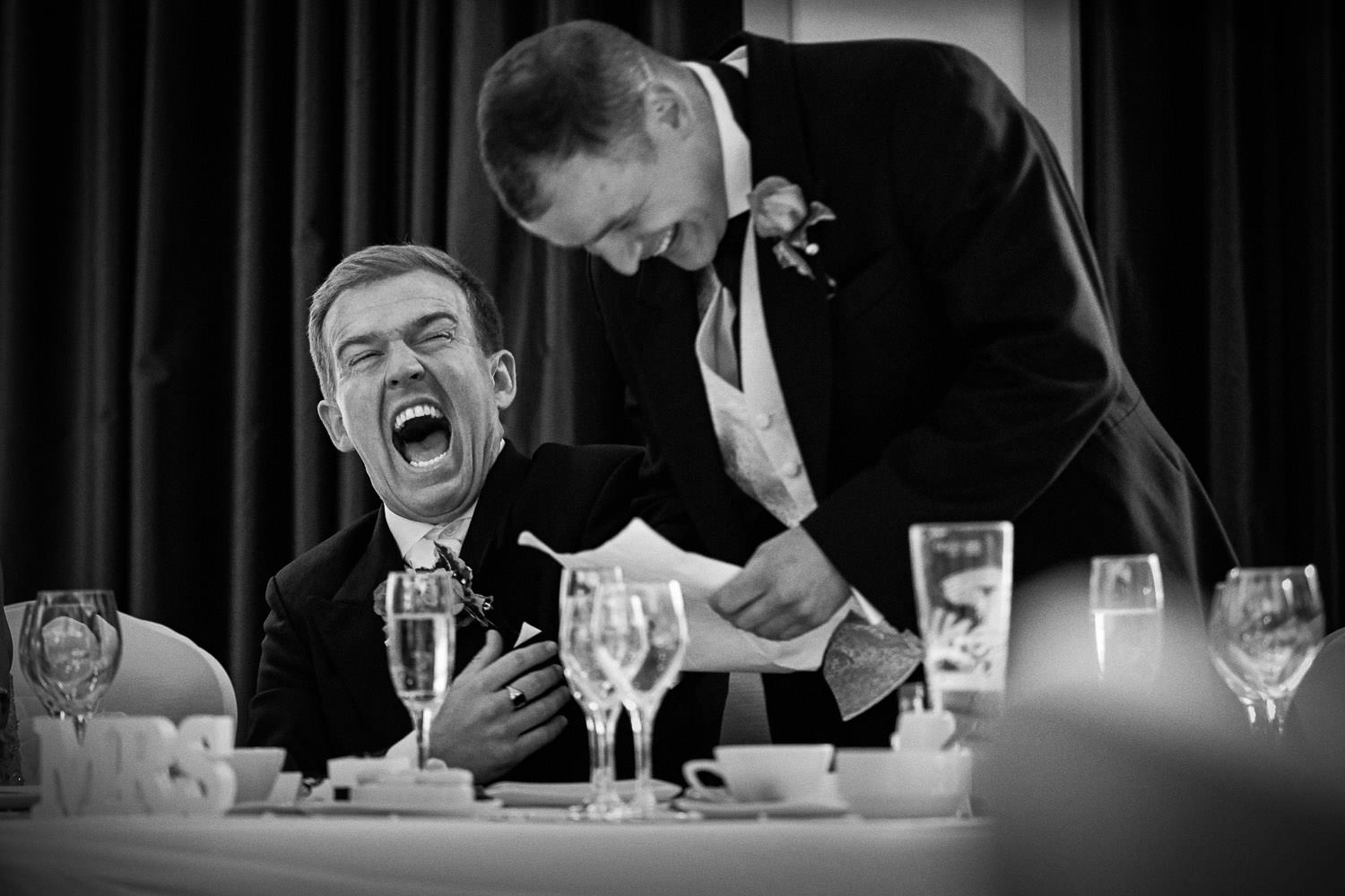 Groom laughing during speeches Liverpool wedding black and white photo