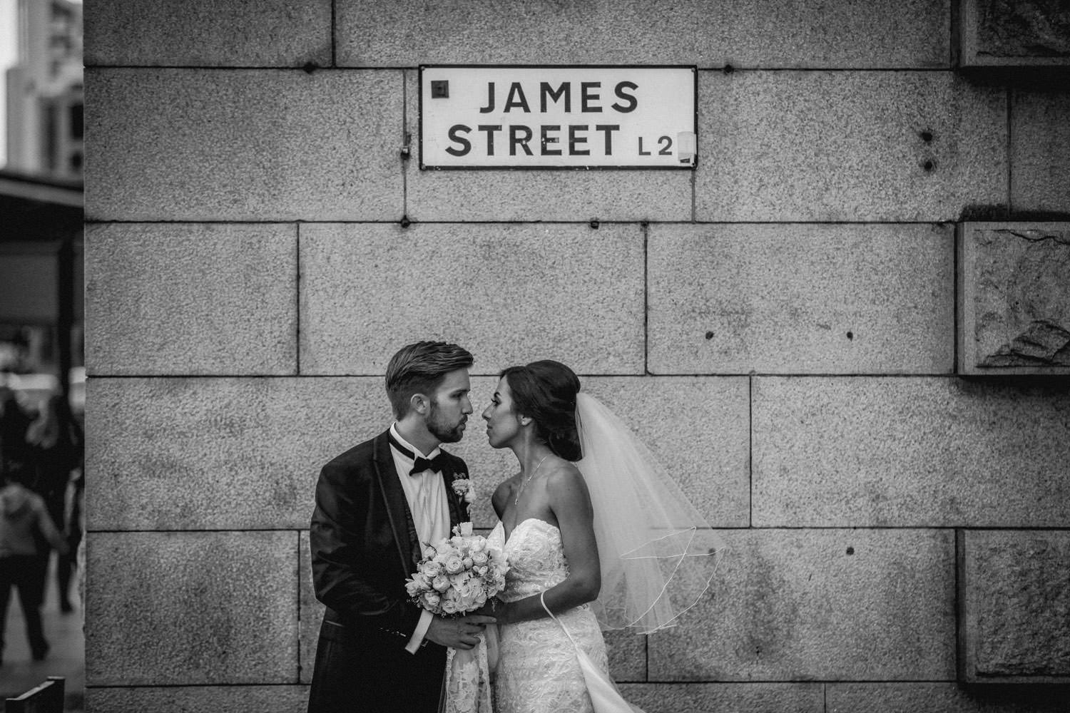 black and white wedding photo Bride and groom on street with 30 James Street sign Liverpool