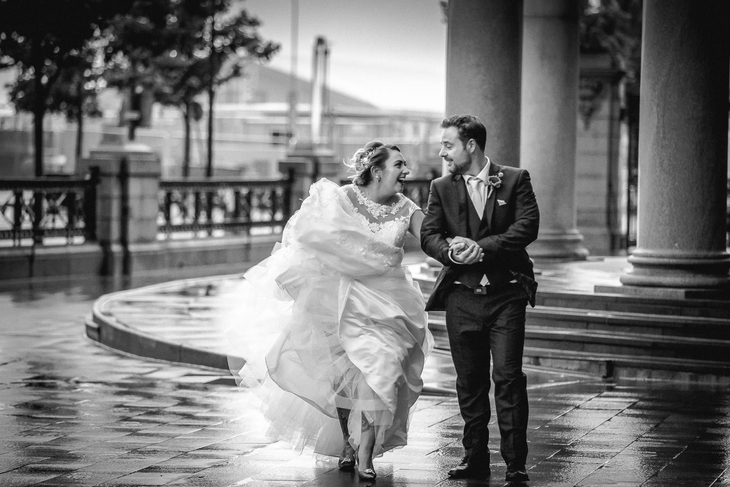 Bride and groom walking in wind with dress blowing outside Royal Liver Building Liverpool wedding