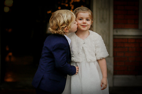 Little boy kissing little girl on check at wedding
