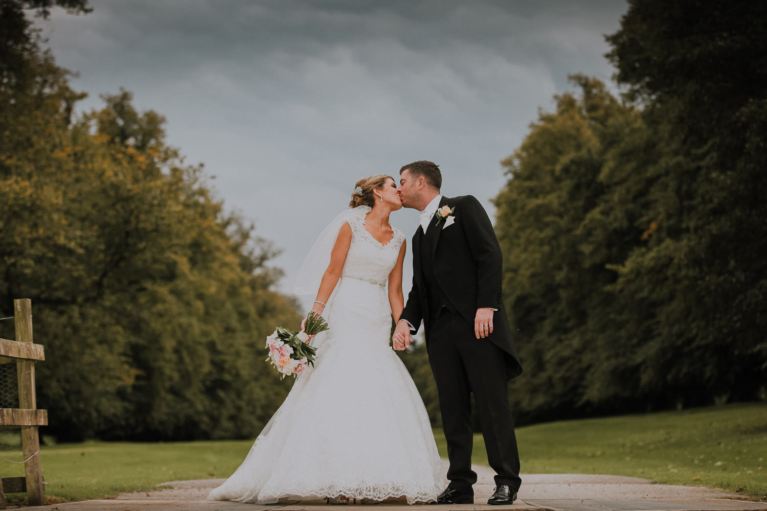 Bride and Groom kissing on the long road at Soughton Hall