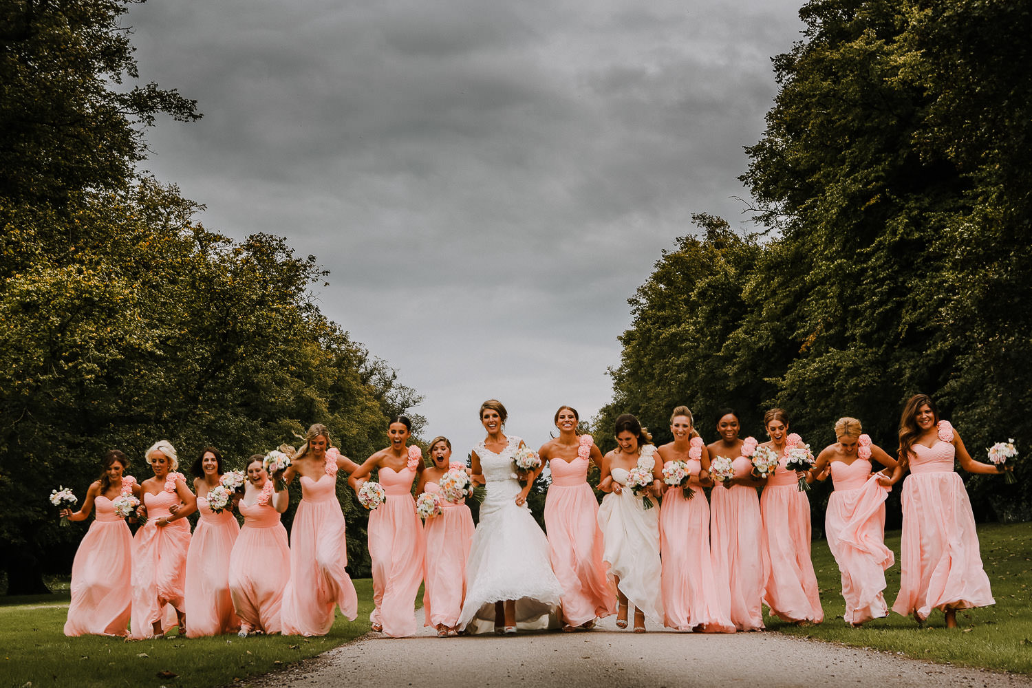 Long line of bride with bridesmaids running at Soughton Hall Cheshire