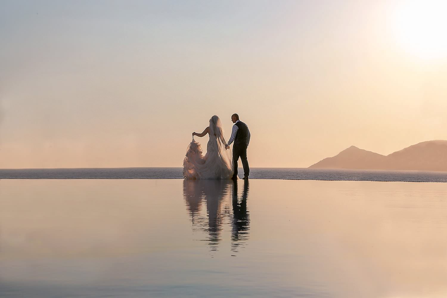 Bride and groom standing on water, infinity pool at sunset