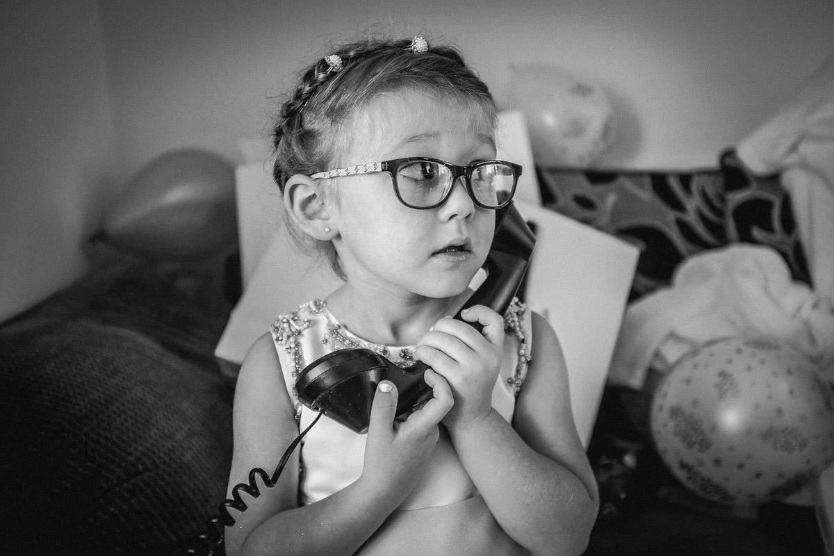 Little girl on phone 2, contact Wes Simpson wedding photographer Liverpool