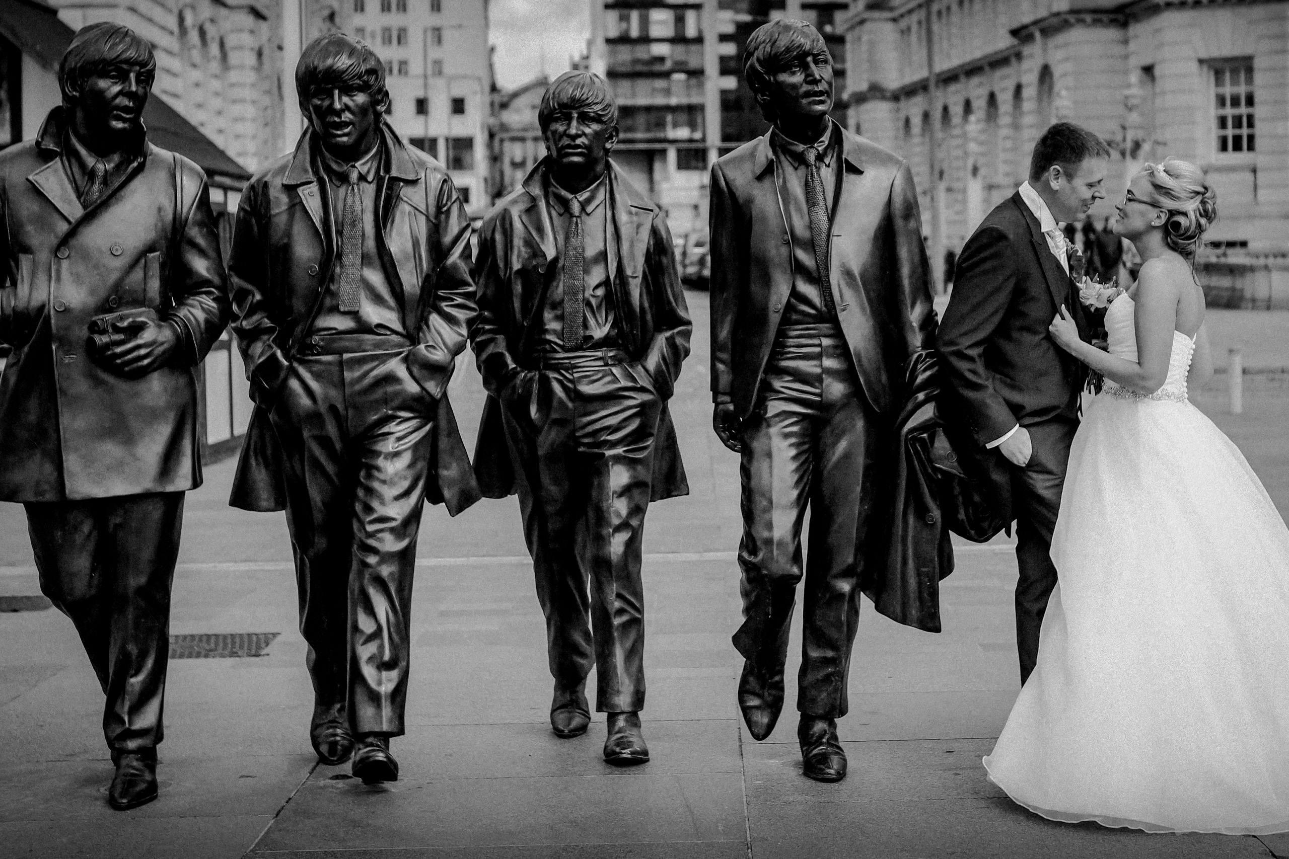 Bride and groom with The Beatles statue Liverpool Pier head
