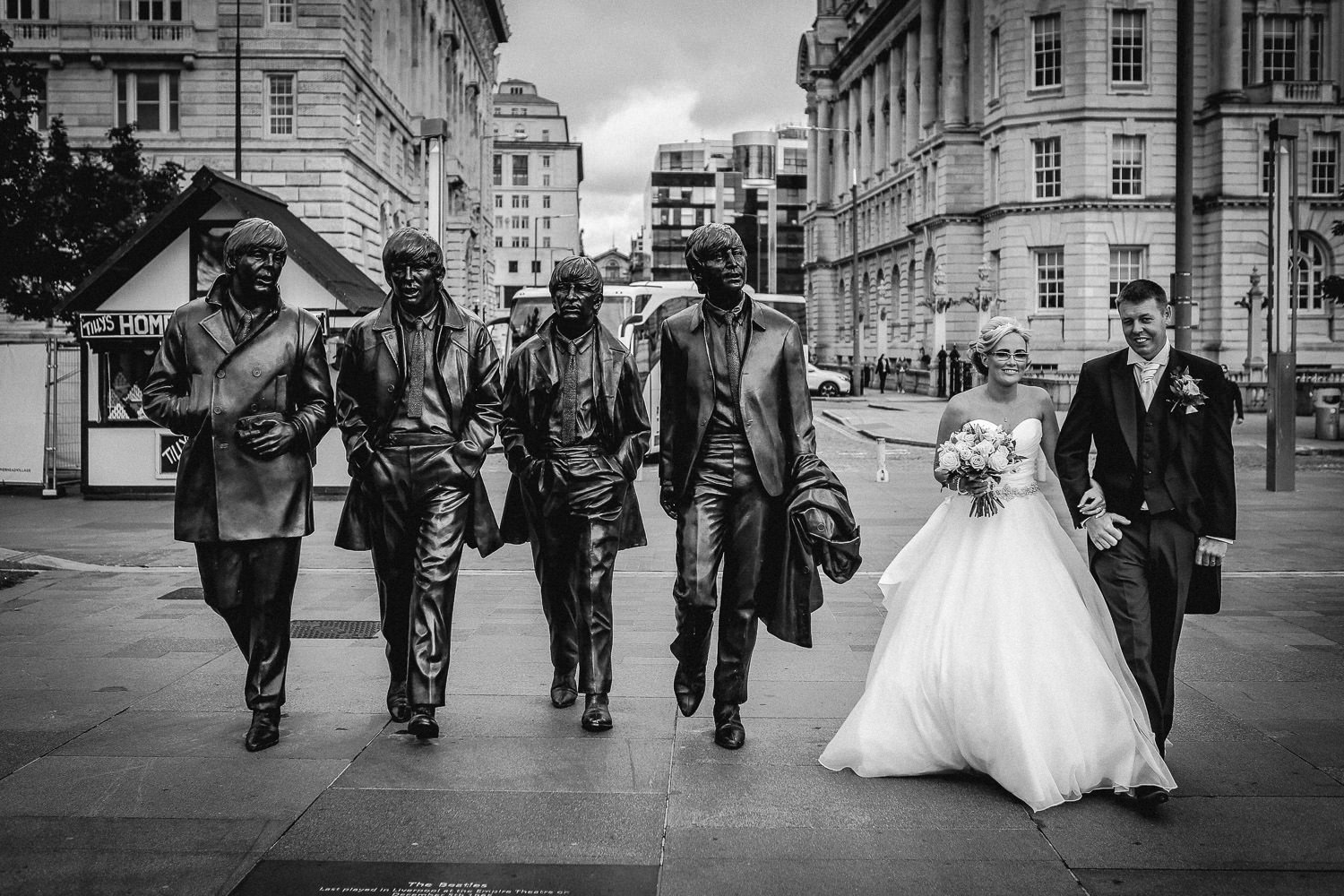 Black and white wedding photography Bride and groom with Beatles Statue in Liverpool on wedding day