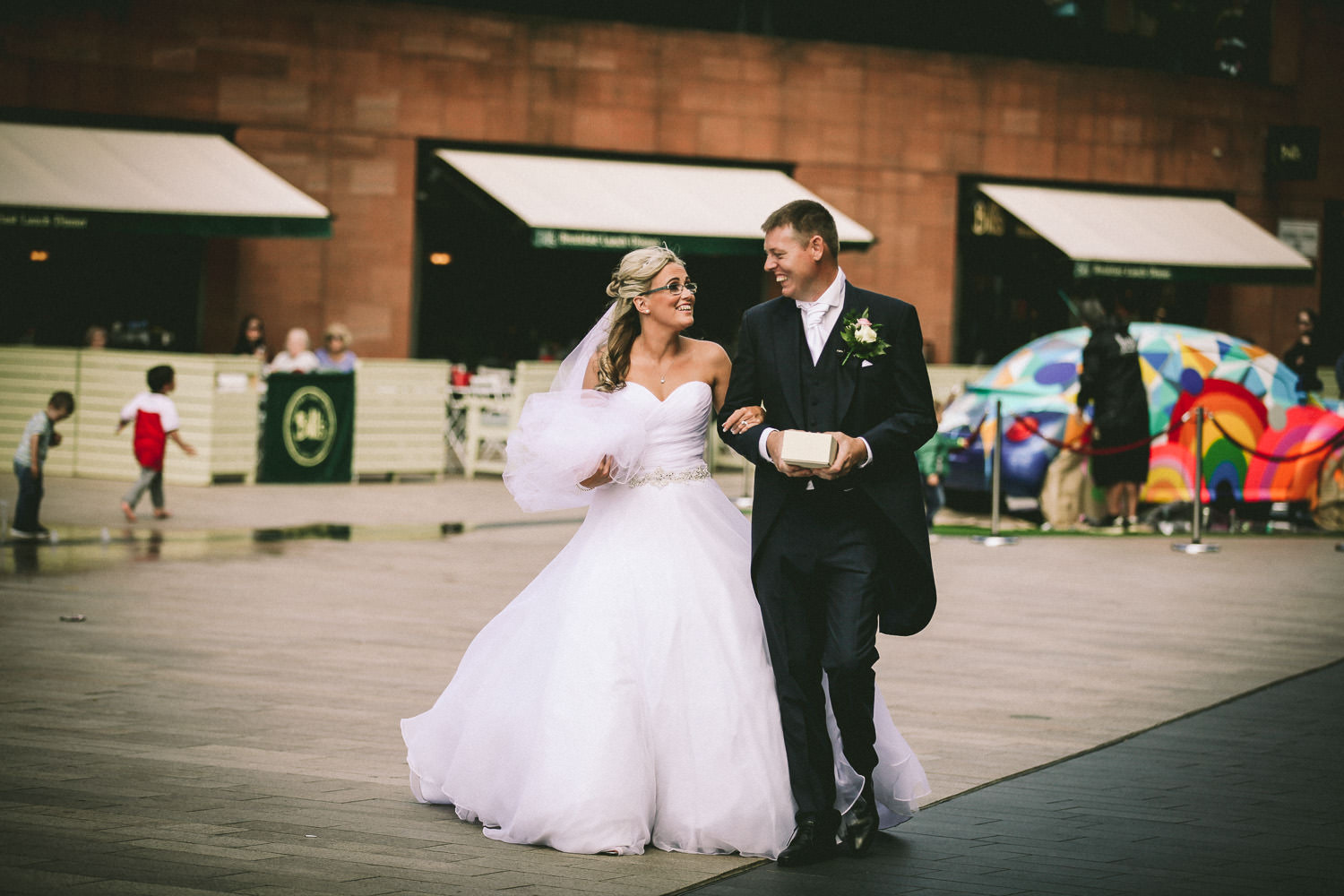 Bride and groom walking Liverpool One. Bride giving Groom gift of Rolex watch