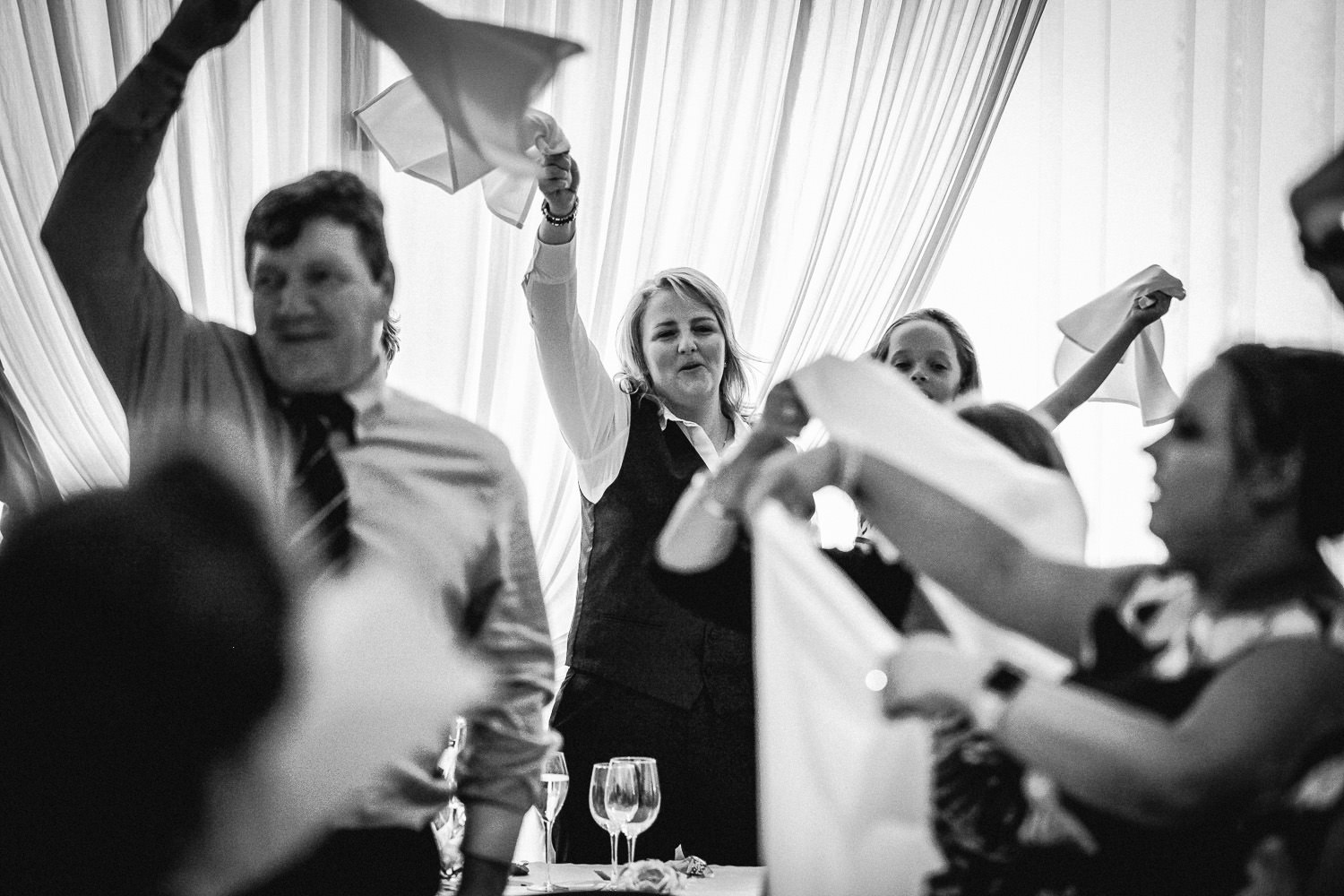 People waving napkins during singing waiters Hilton Liverpool wedding
