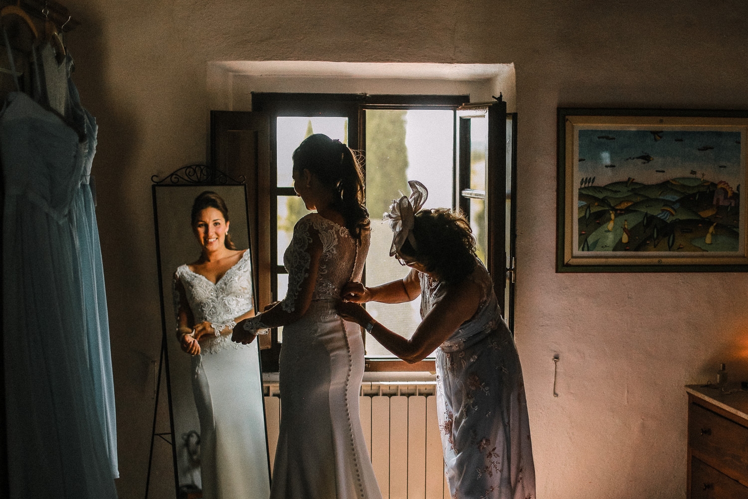 Mum helping daughter into her Essence of Australia wedding dress at Fattoria la loggia in Tuscany