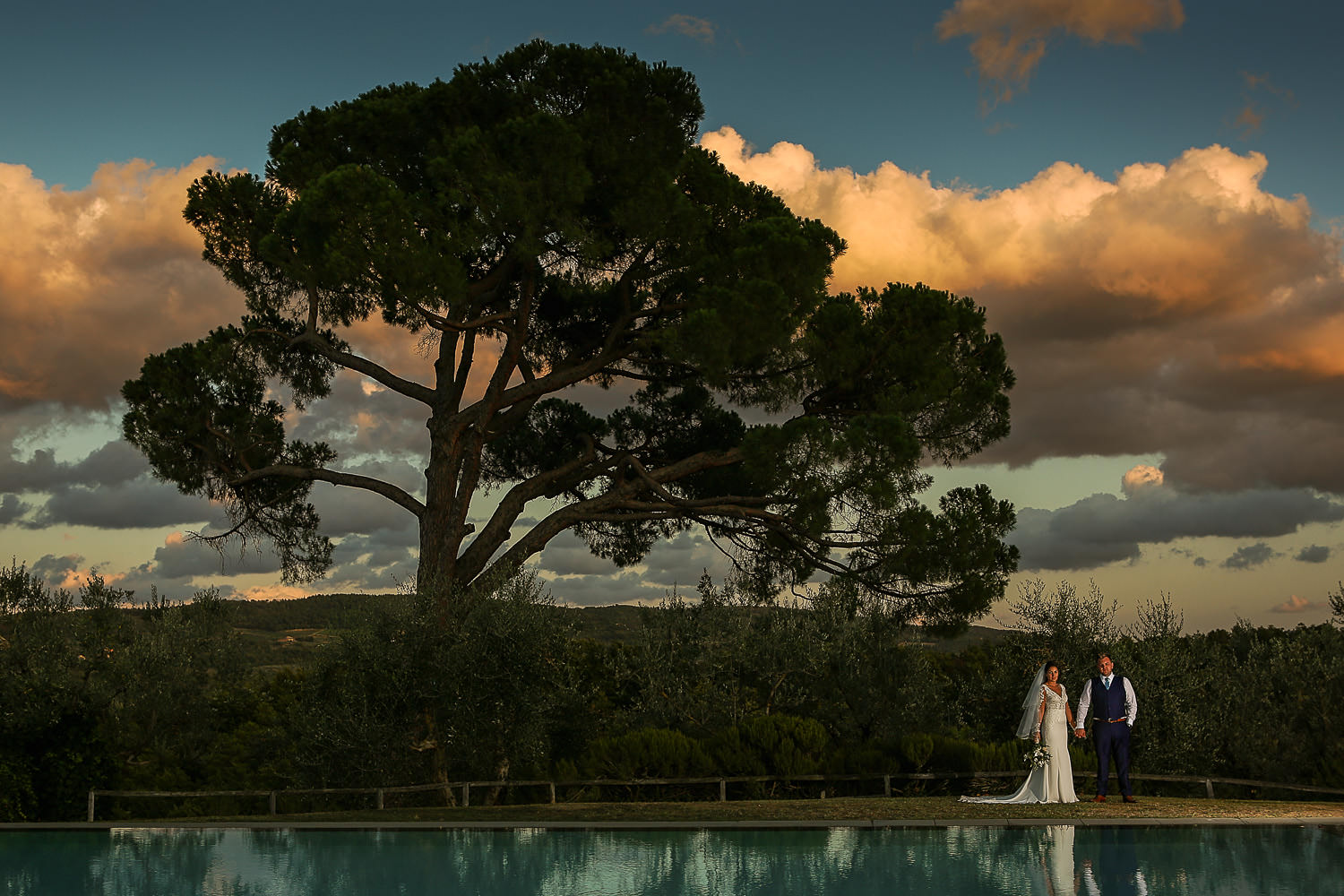 wedding photography Tuscany Bride and groom standing under big tree at Fattoria la loggia wedding venue Tuscany