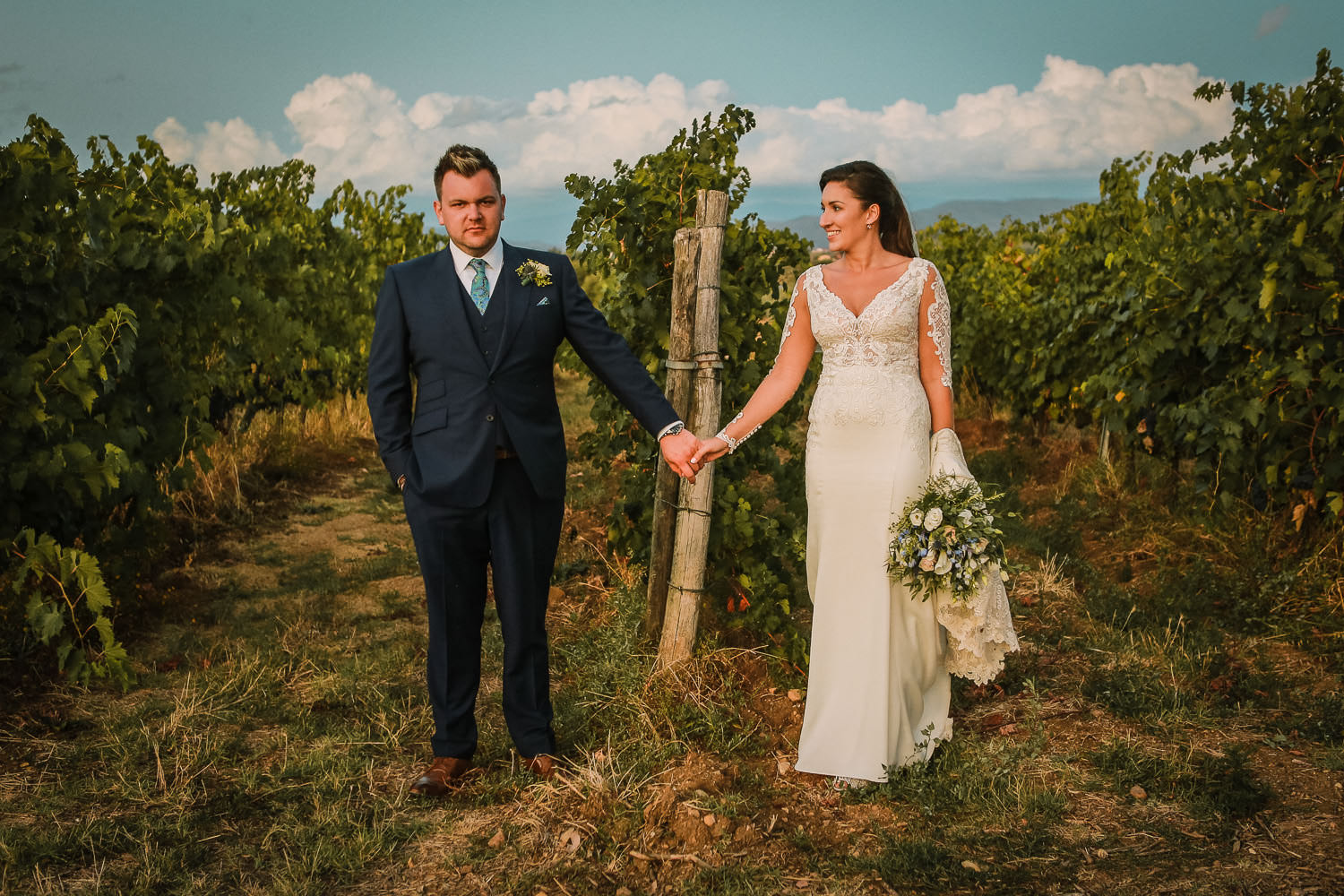 Bride and Groom holding hands in Vine Yards of Tuscany during wedding at Fattoria la Loggia