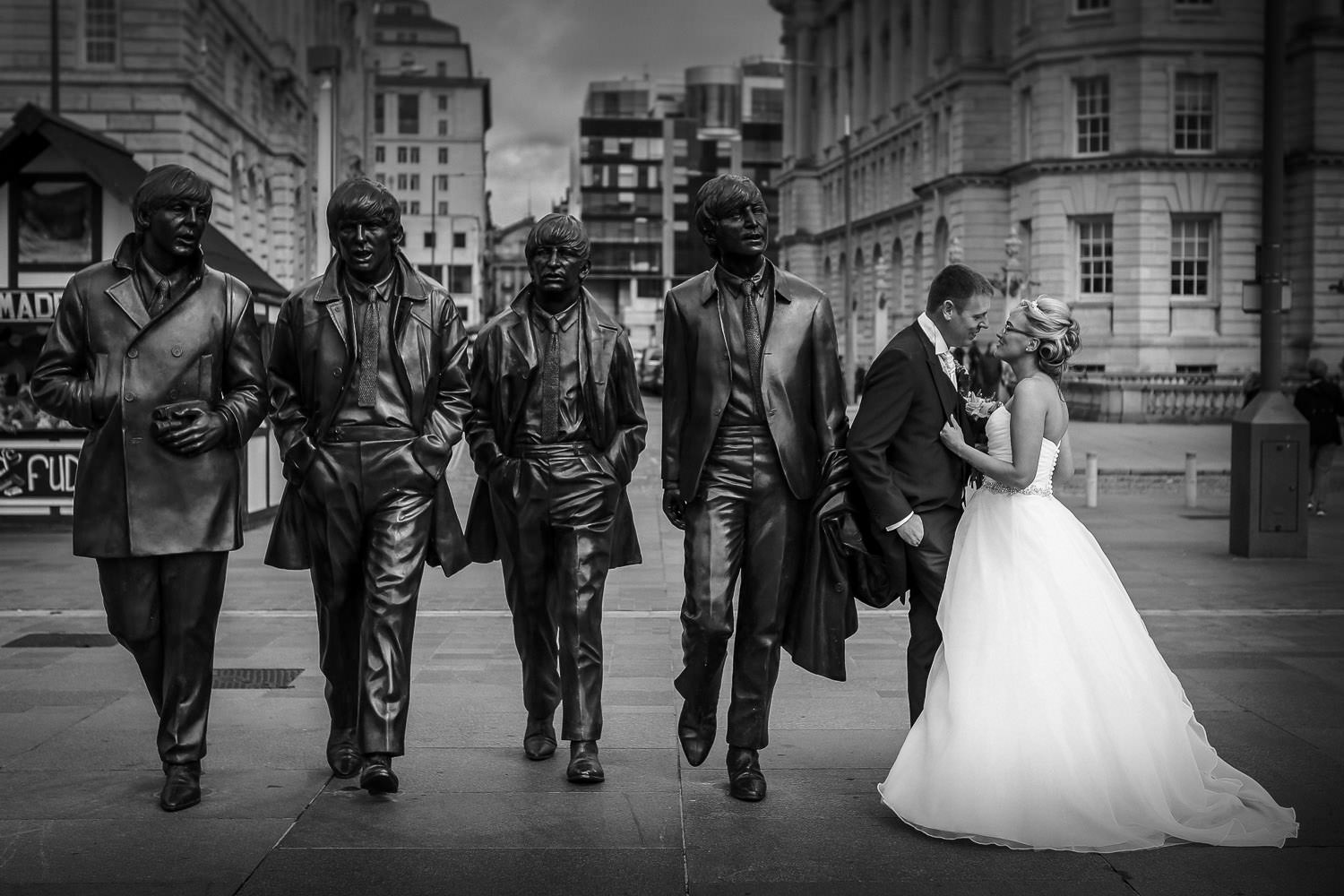 Bride and groom with Beatles statue in Liverpool by Liverpool wedding photographer Wes Simpson