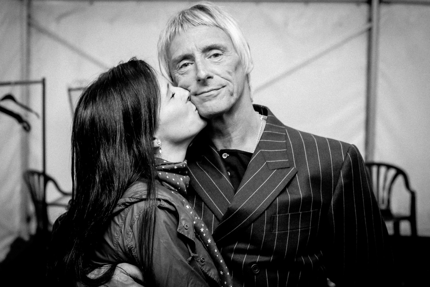 Black and white photo of Paul Weller wife kissing him by Celebrity wedding photographer Wes Simpson