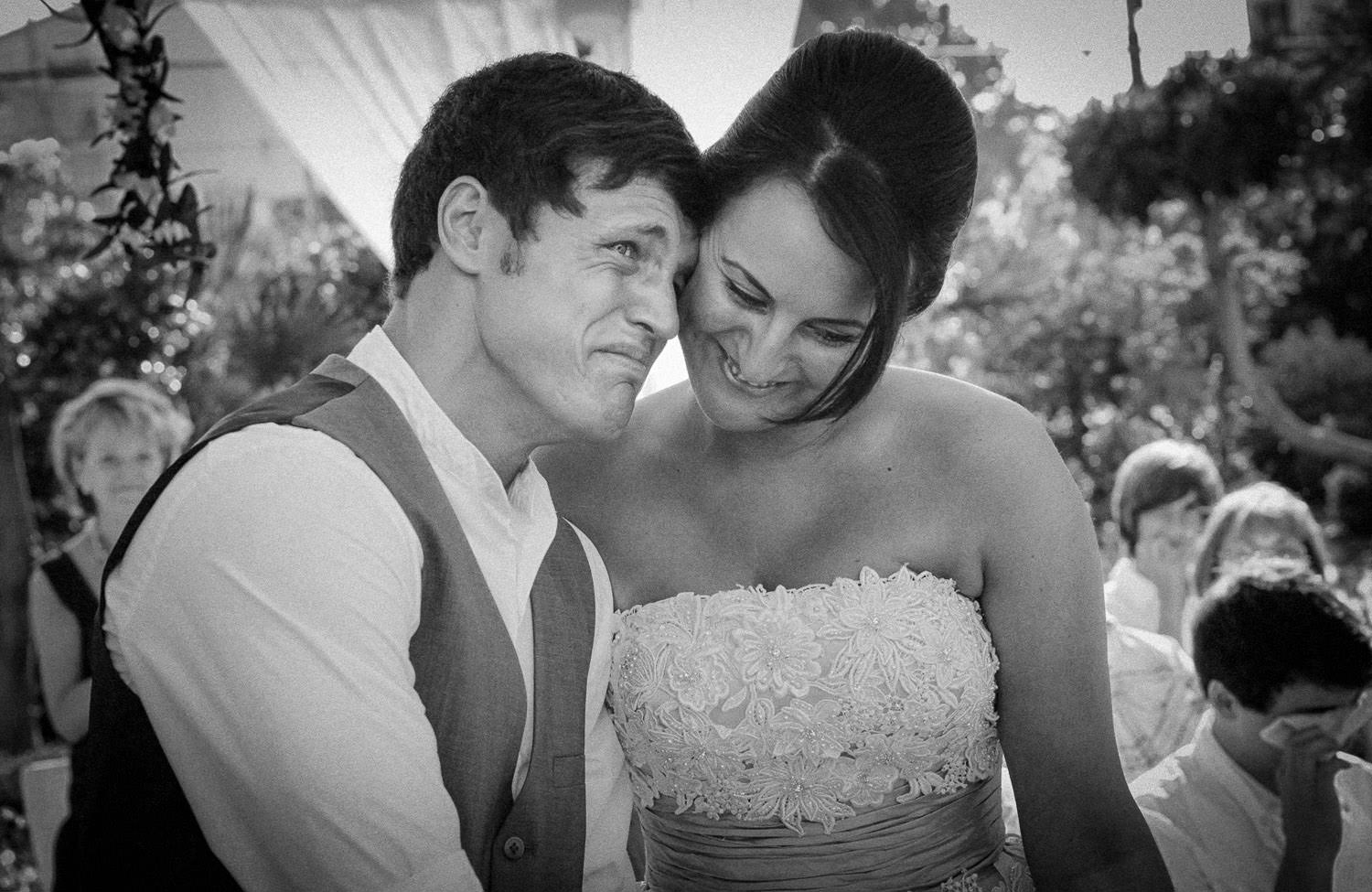 black and white photo of emotional groom crying with bride