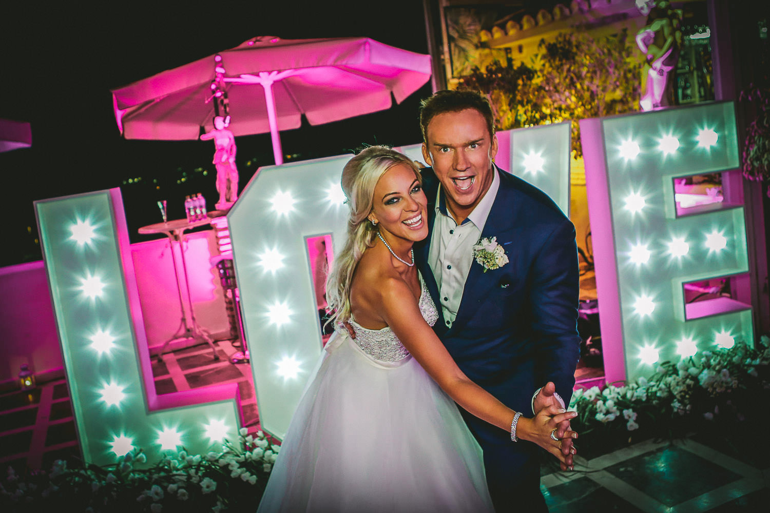 Celebrity wedding photographer, photo of Louise and Russell Watson with love sign on wedding night