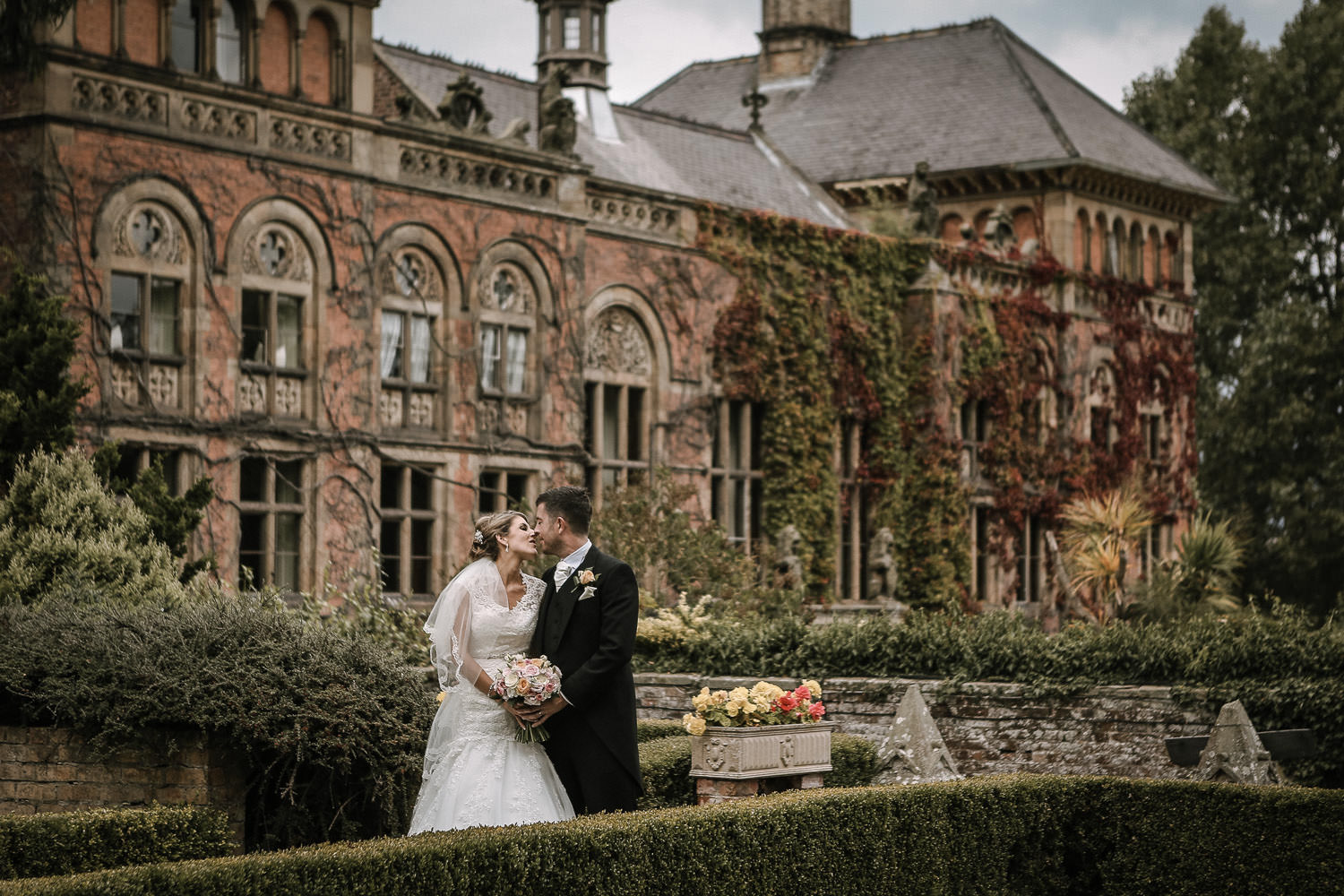Cheshire wedding photographer. Bride and groom kissing in the garden of Soughton Hall wedding venue