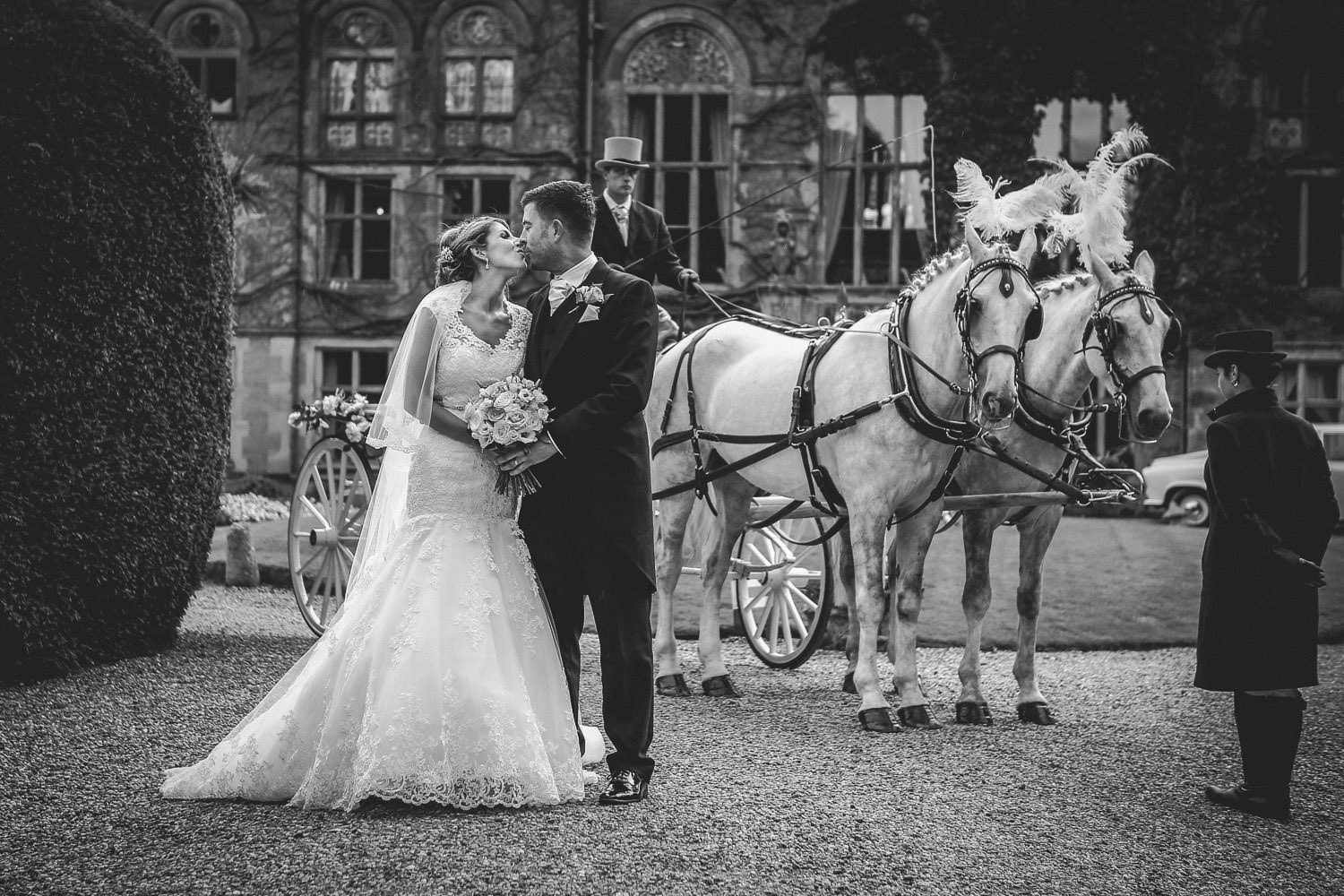 Cheshire wedding photographer: Black and white photo of bride and groom kissing in front of Soughton Hall with horses