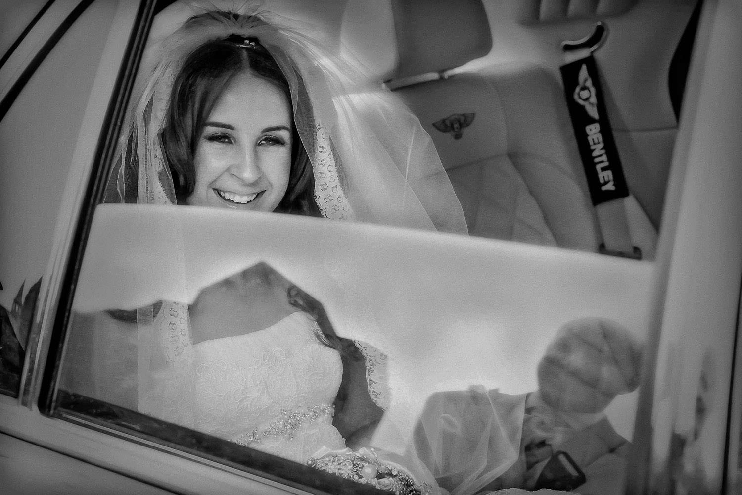 Bride looking out of car Bentley wedding car window