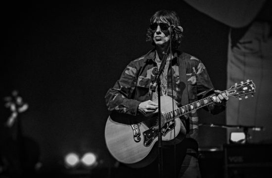 Richard Ashcroft singing wearing army jacket with a guitar on stage in Manchester