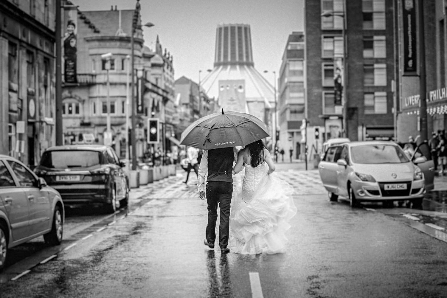 Liverpool wedding photographer. Bride and groom walking down Hope st Liverpool in the rain with unberella