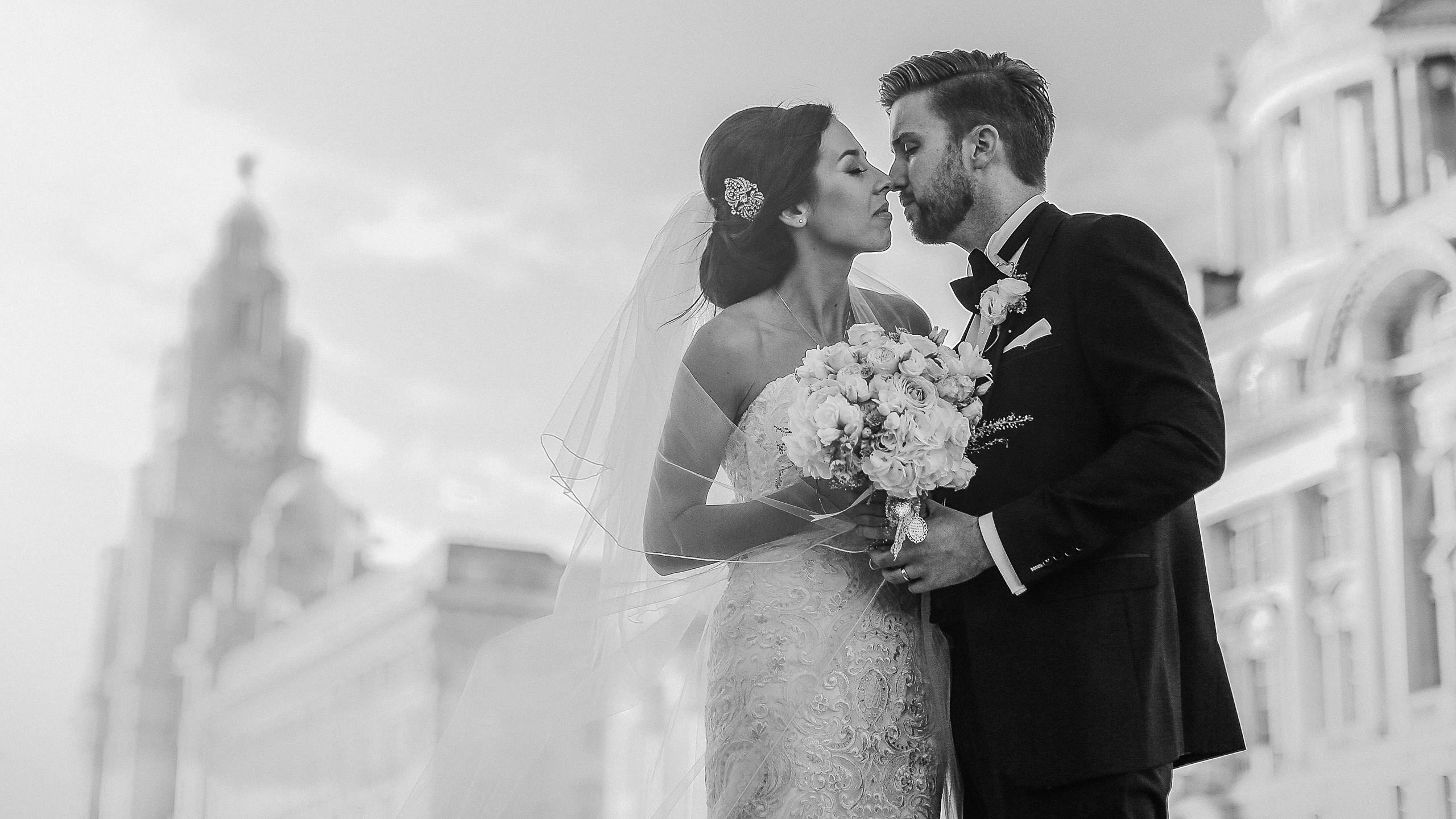Liverpool wedding photographer. Black and white photo bride and groom kissing Liverpool Pier Head in front of Royal Liverbuilding