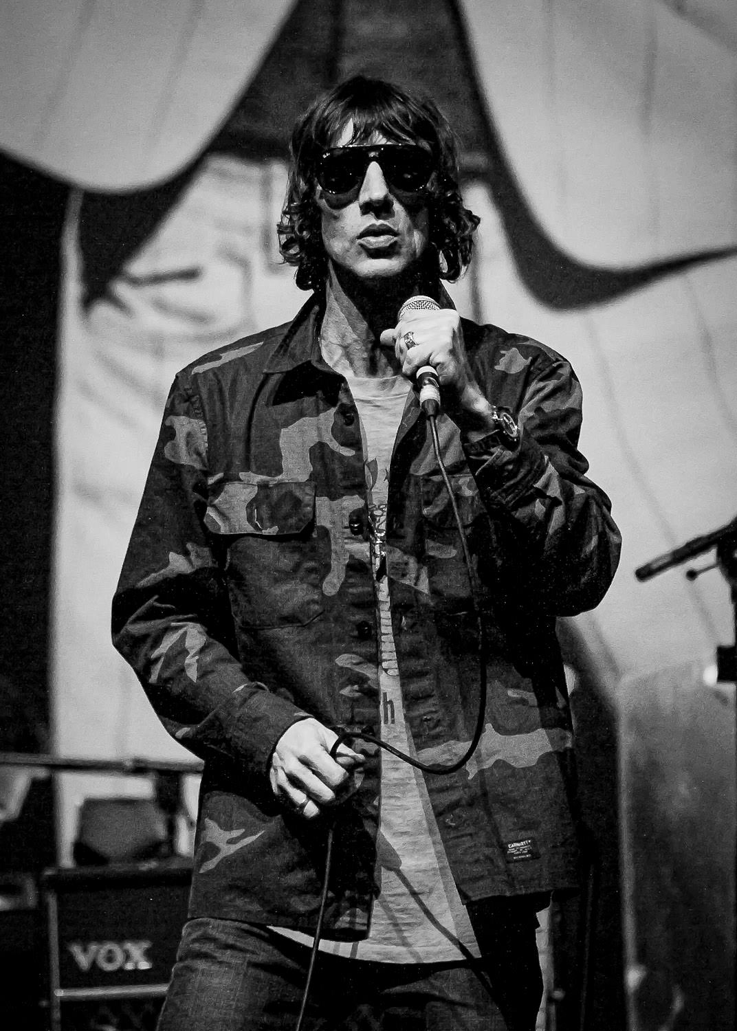 Richard Ashcroft singing on stage wearing army jacket in Manchester