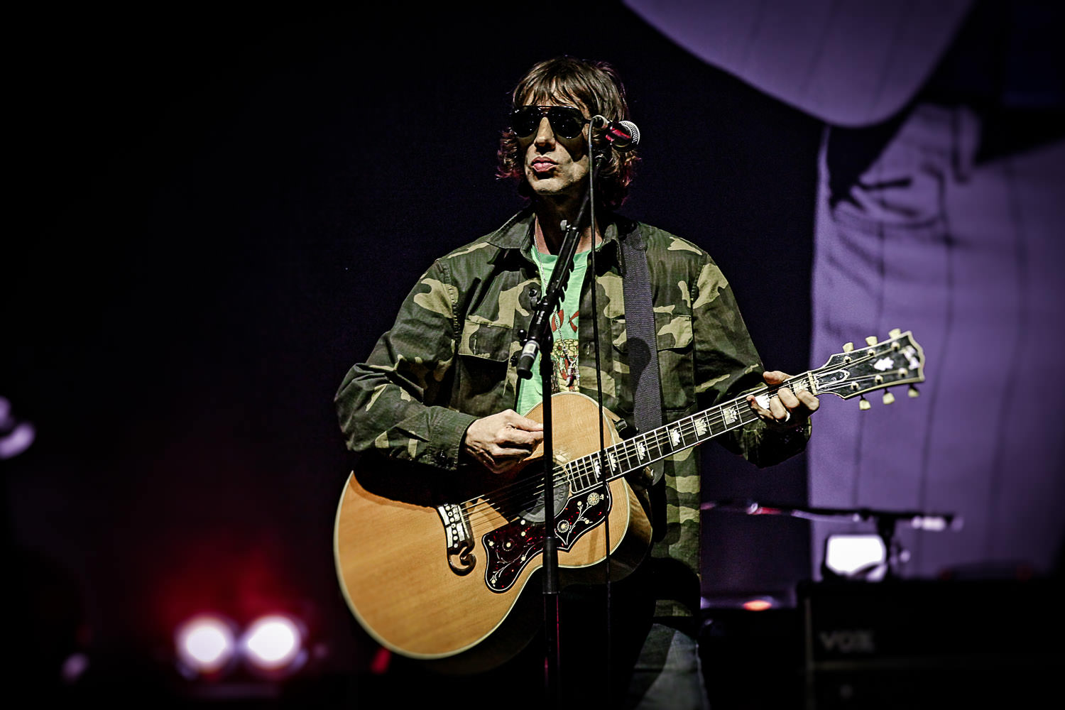 Richard Ashcroft wearing army jacket singing on stage in Manchester