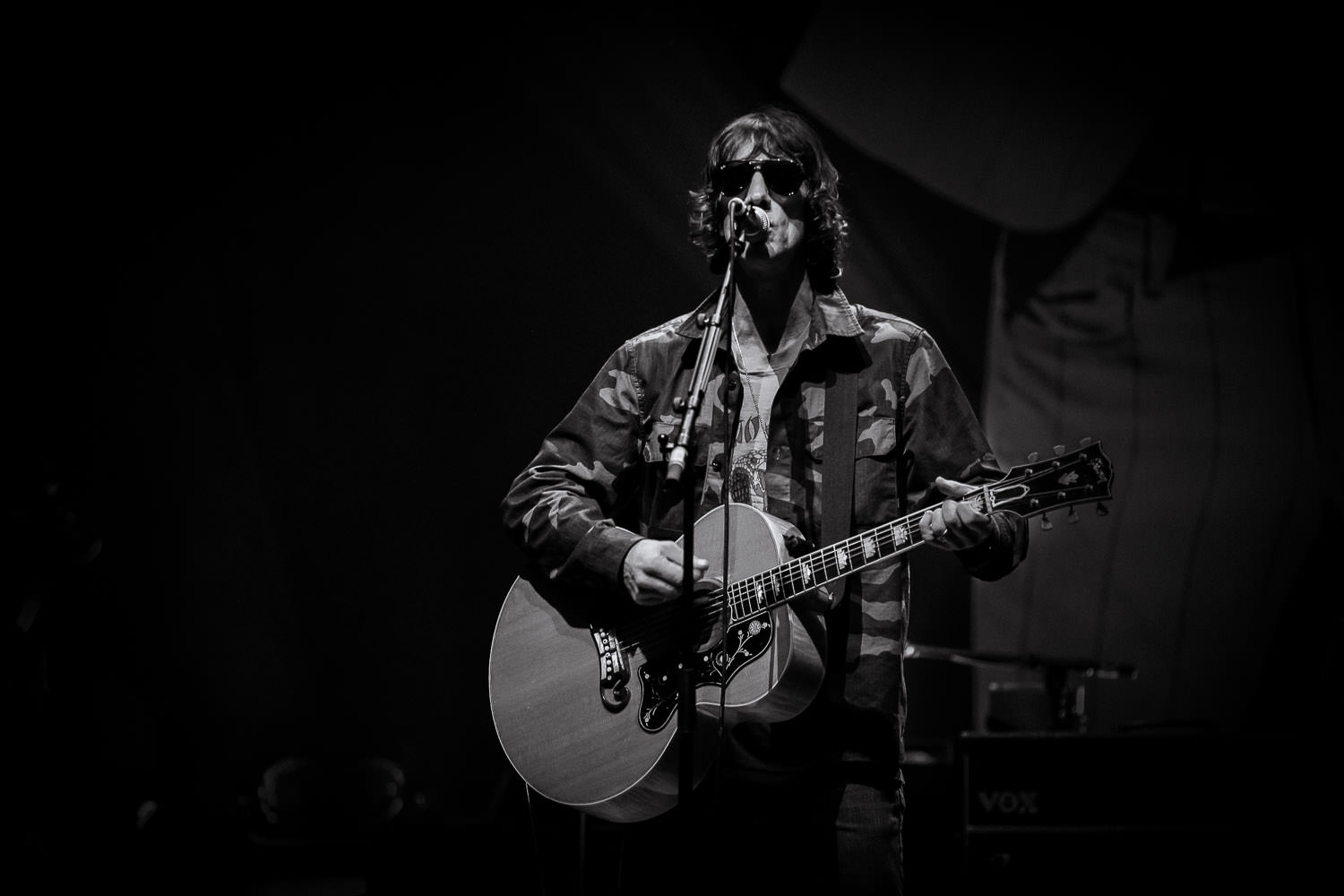 Black and white photo of Richard Ashcroft wearing army jacket singing on stage in Manchester