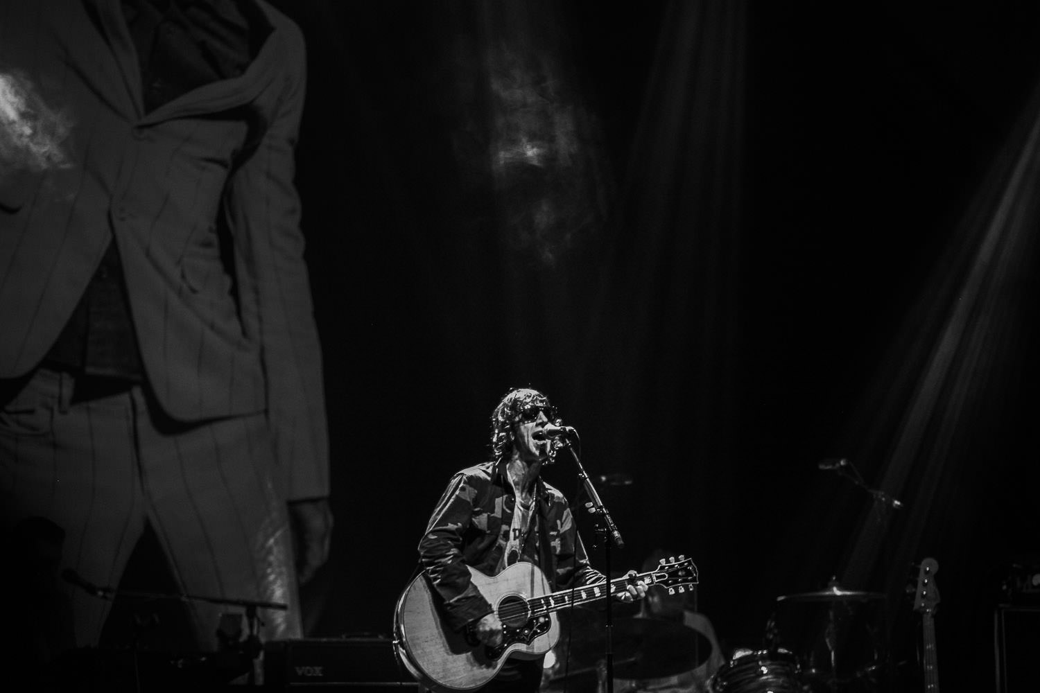 black and white photo of Richard Ashcroft singing on stage with guitar