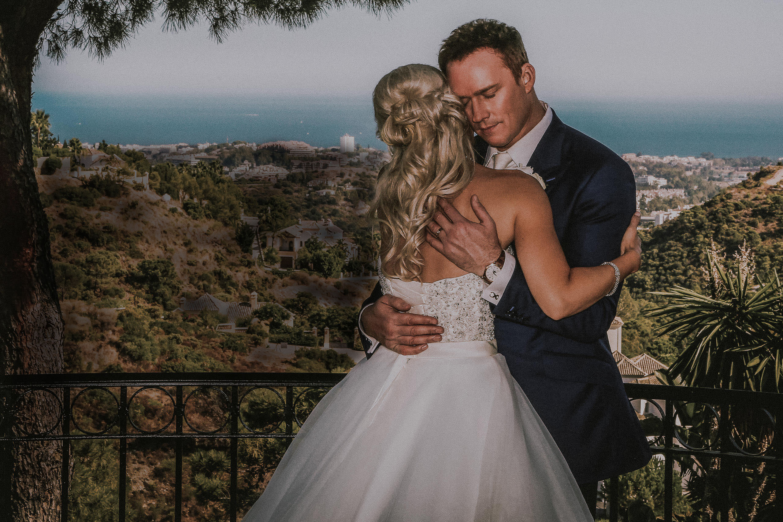 Celebrity wedding photographer. Bride and groom Russell watson romantic hug with vista views of Marbella