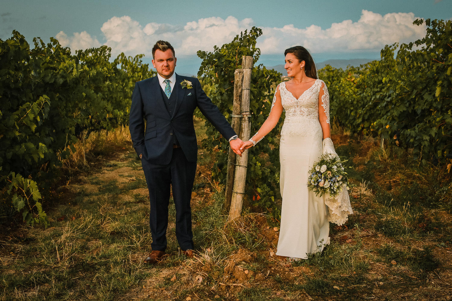Bride and Groom in Tuscany Vine yard holding hands