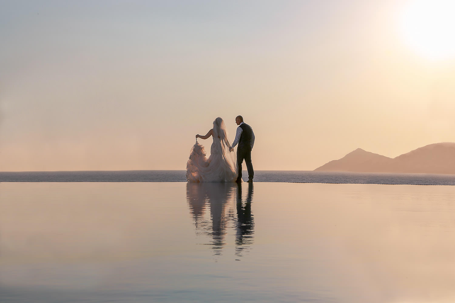 Bride and groom infinity pool reflection photo at sunset Liberty Lykia Turkey