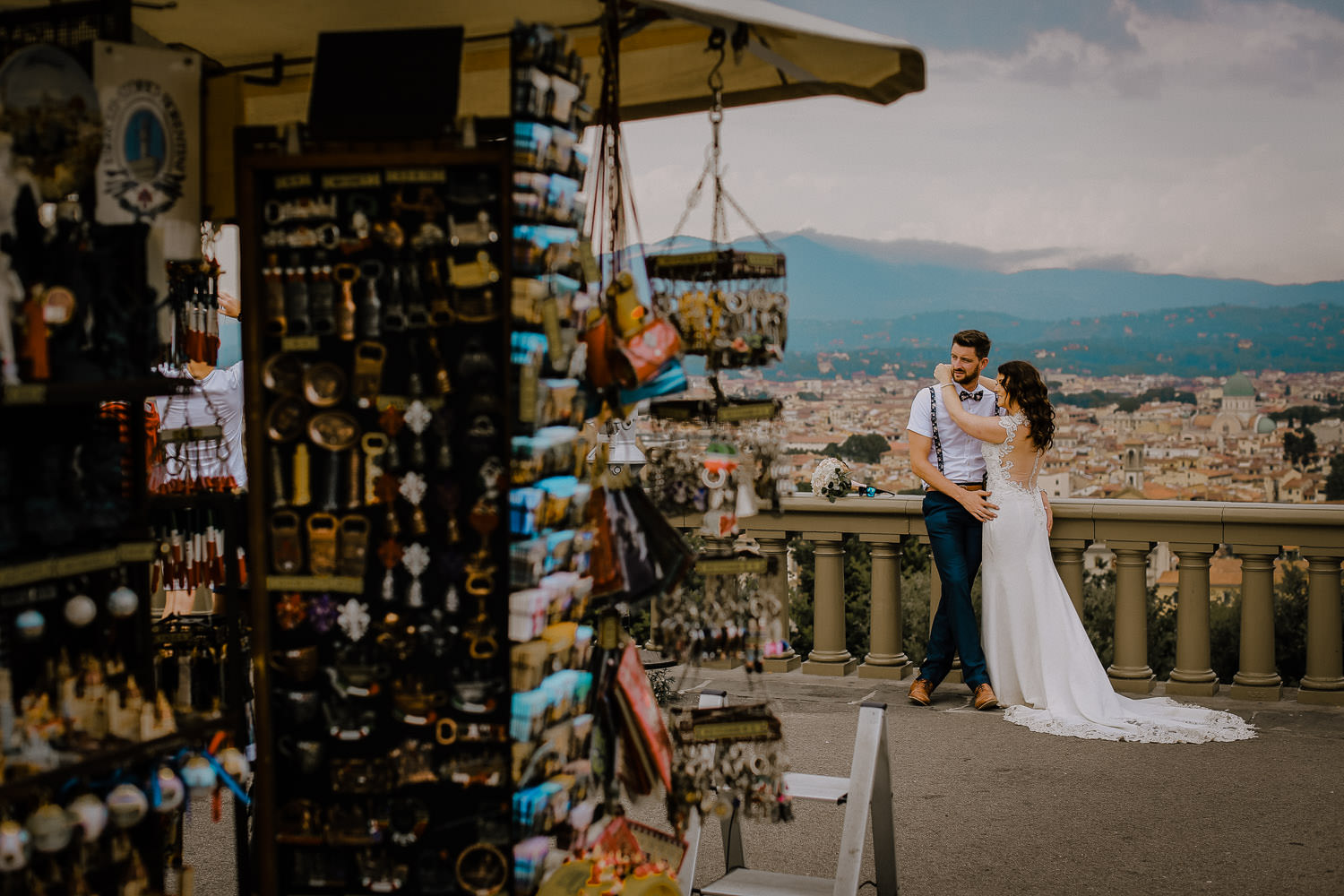 Destination wedding photographer, photo Bride and groom behind souvenir shop in florence