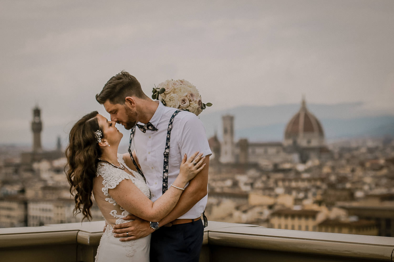 Destination wedding photographer. Bride and groom kissing with view of Florence Italy