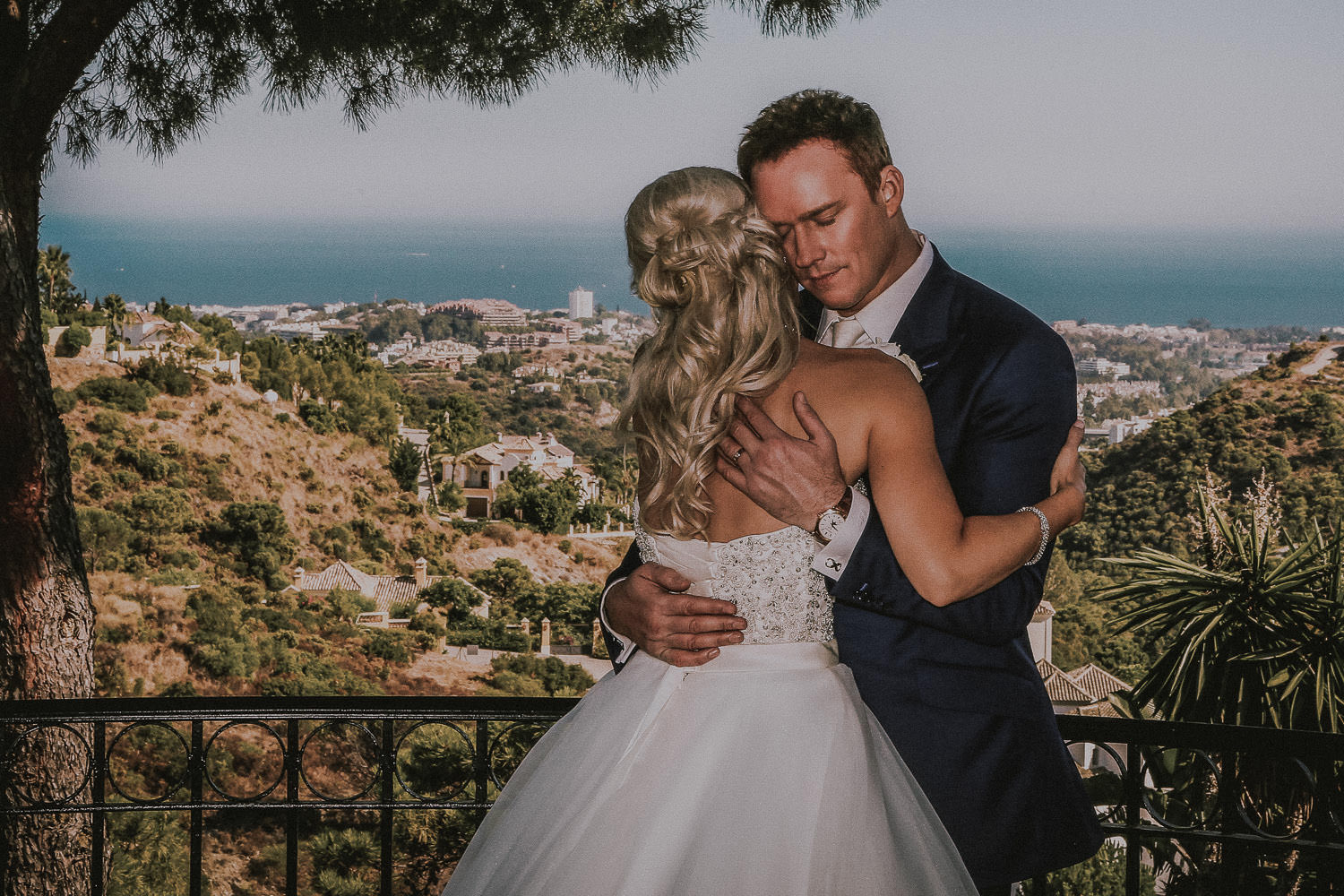Celebrity destination wedding photographer. Bride and groom hugging with view of Marbella